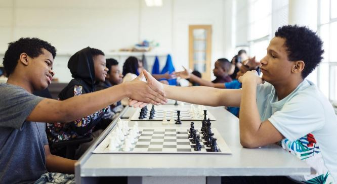 Two black teenagers shake hands prior to starting chess game