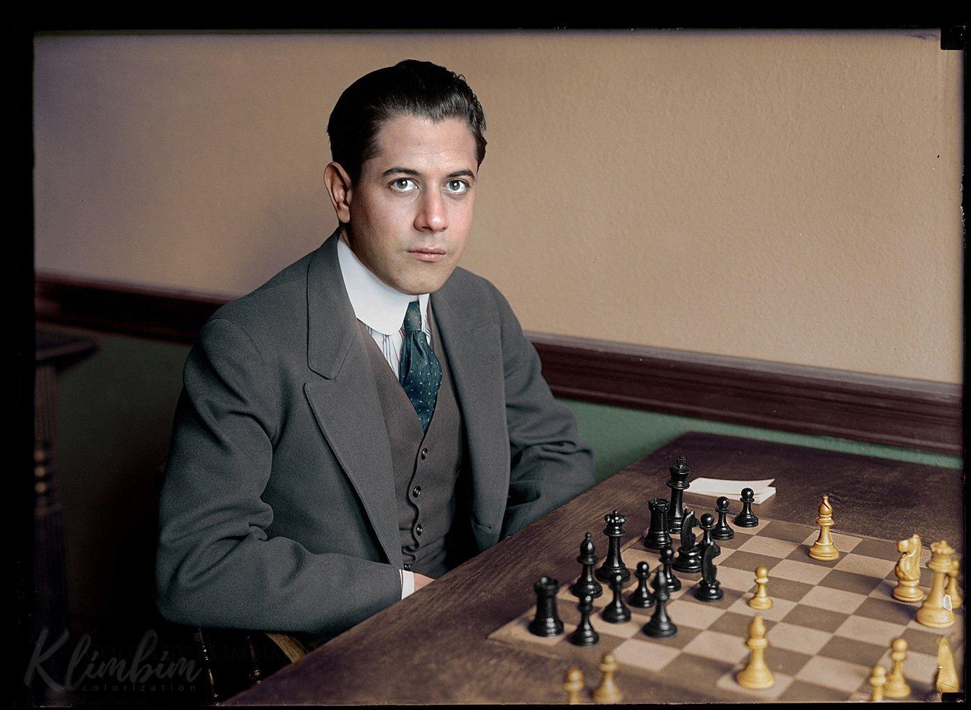 José Raúl Capablanca sitting at chessboard behind the black pieces