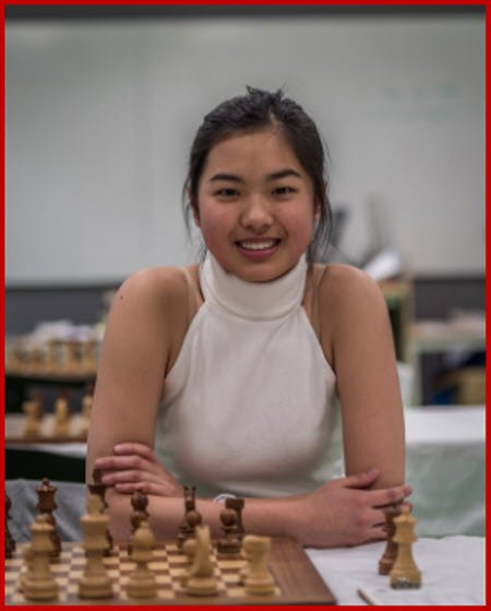 Qiyu Zhou in white top at chessboard behind black pieces