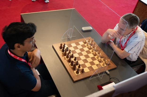 two players behind plexiglass shield one with hand to mouth ready to start a chess game